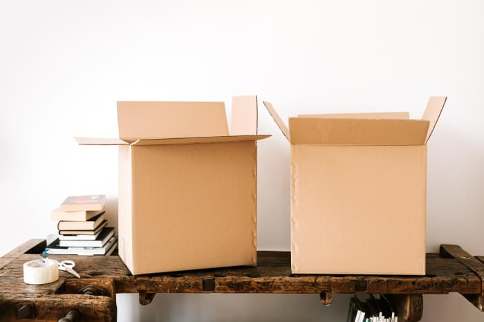 Two open moving boxes on a table. To the left of them, there is a small pile of books as well as scissors and scotch tape.